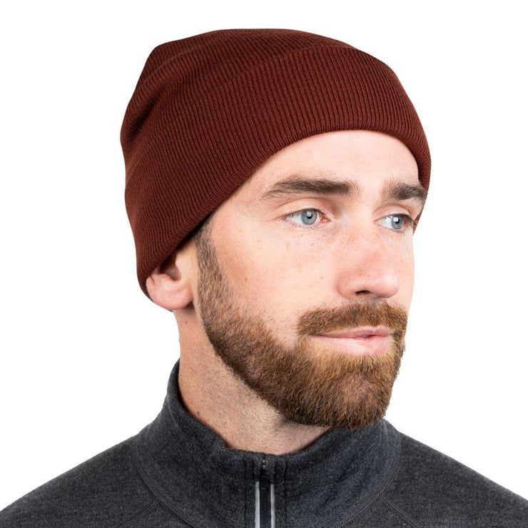 man wearing a rust colored merino wool ribbed knit beanie