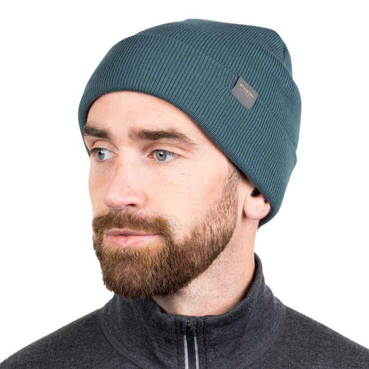 man wearing a teal merino wool ribbed knit beanie