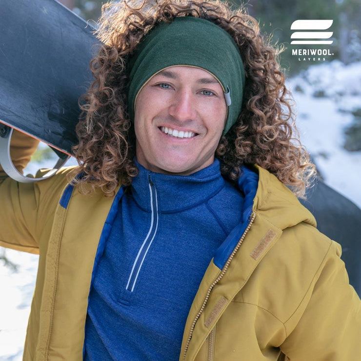 man outside with a snowboard wearing a army green and sand reversible merino wool headband
