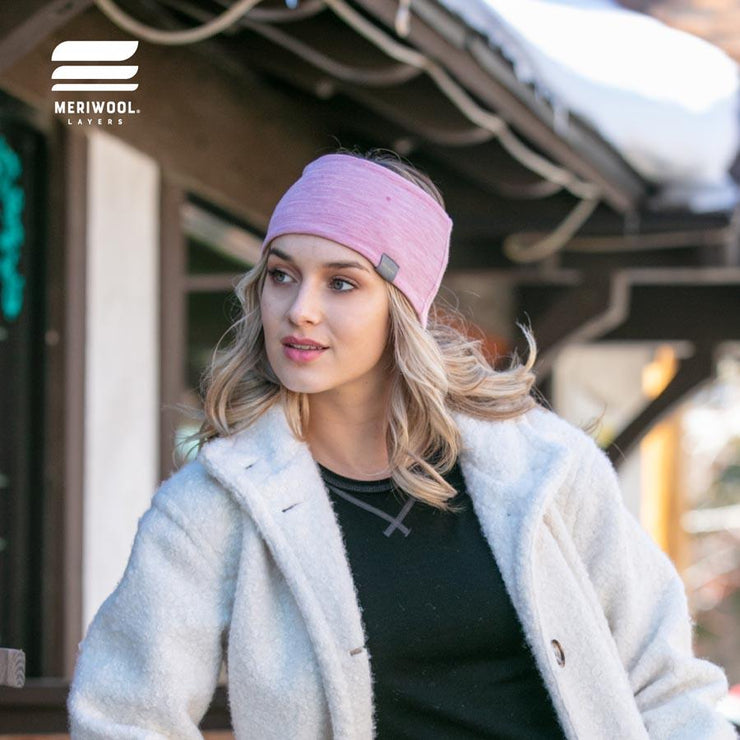 woman outside in winter wearing a pink and khaki reversible merino wool headband