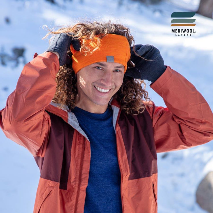 man outside in the snow wearing an orange merino wool headband