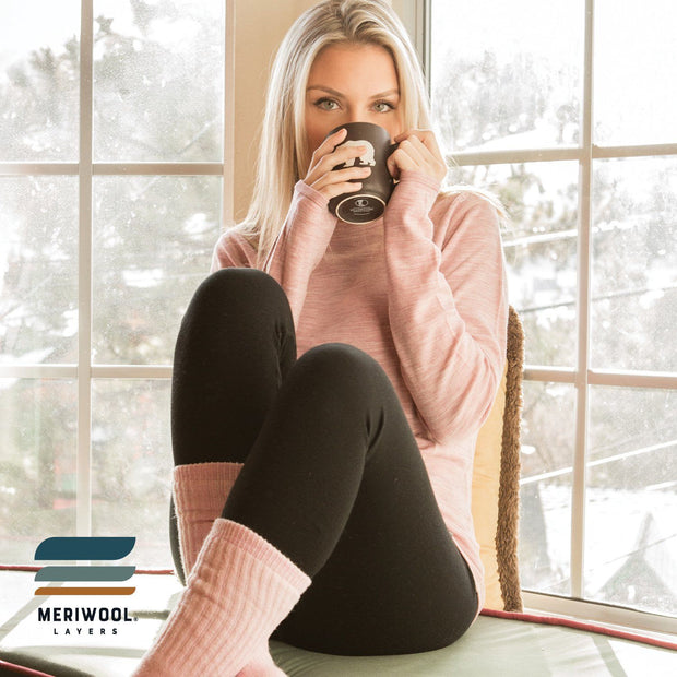woman indoors wearing a pair of women's black merino wool 400 heavyweight base layer bottoms