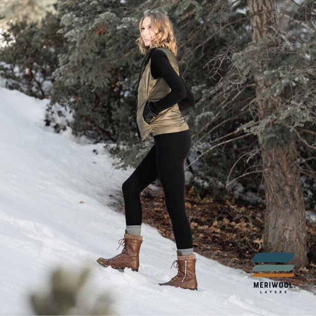 woman in the snow wearing a pair of women's black merino wool 400 heavyweight base layer bottoms