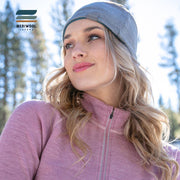 woman in the snow wearing a women's pink heather merino wool 400 base layer half zip sweater and headband