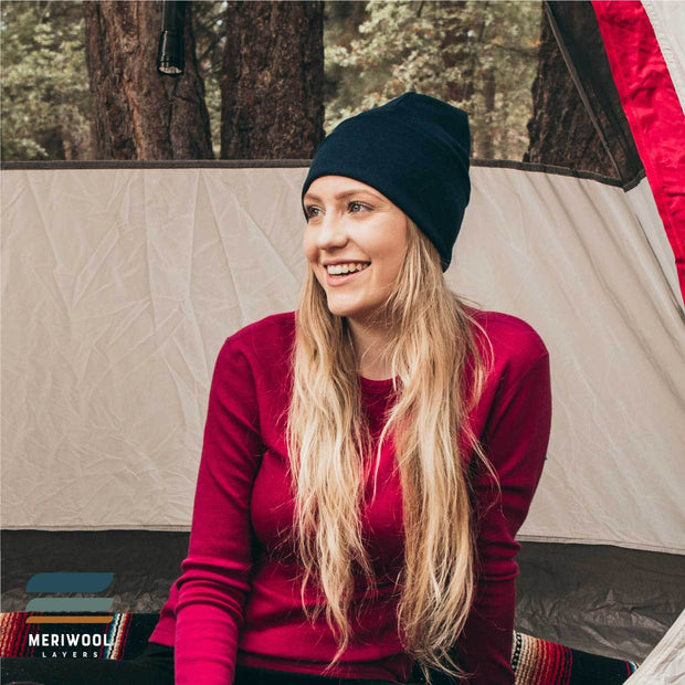 woman in a tent camping wearing a navy blue merino wool 250 cuffed beanie