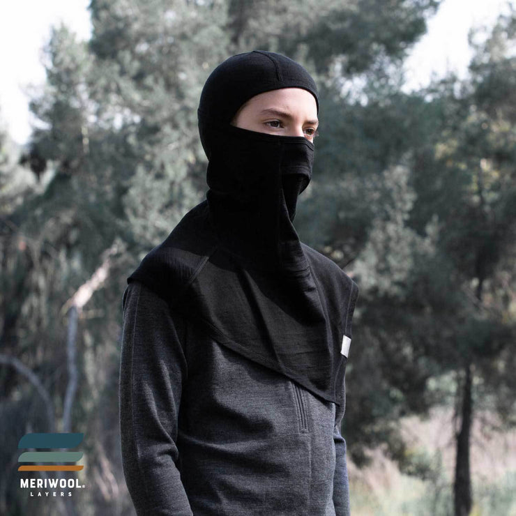 teenager standing outside young adult wearing a black merino wool 200 youth balaclava face mask