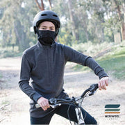 teenager on a bike wearing a black merino wool 200 youth balaclava face mask with a helmet