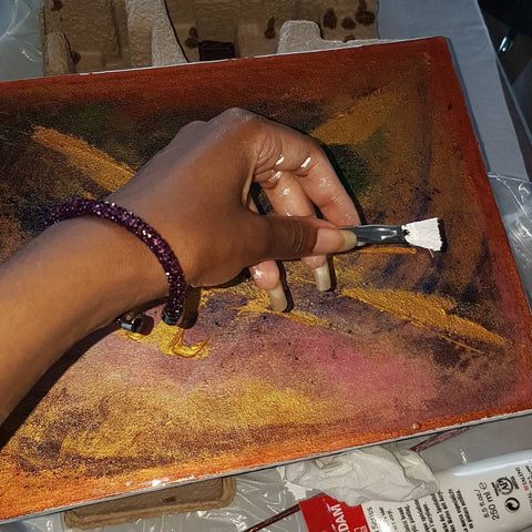 Safi Nakihimba hand holing brush used to paint artwork she created - 2017