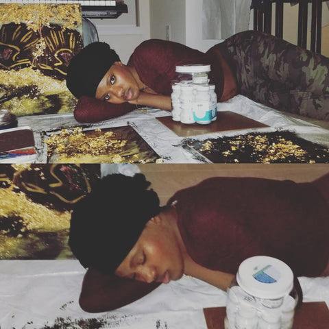 Safi Nakihimba laying down on the floor with her mixed media art pieces; 1 pose her eyes are open, the other her eyes are closed.