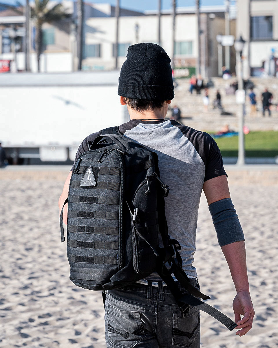 A man in an urban city uses his 14er Tactical Black Backpack as a bug out bag during an emergency.