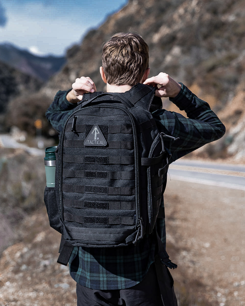 A man in a rural setting uses his 14er Tactical Black Backpack as a bug out bag during an emergency.