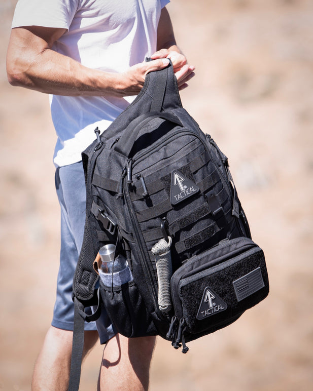 : A 14er Tactical Backpack for EDC is held by a man in the outdoors, his water bottle tucked into a side pocket.