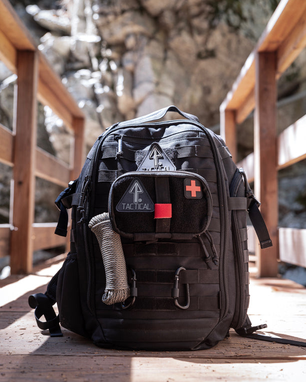 :A 14er Tactical Backpack for EDC sits on a bridge in the mountains, its MOLLE straps holding gear, including the IFAK Pouch and rope.