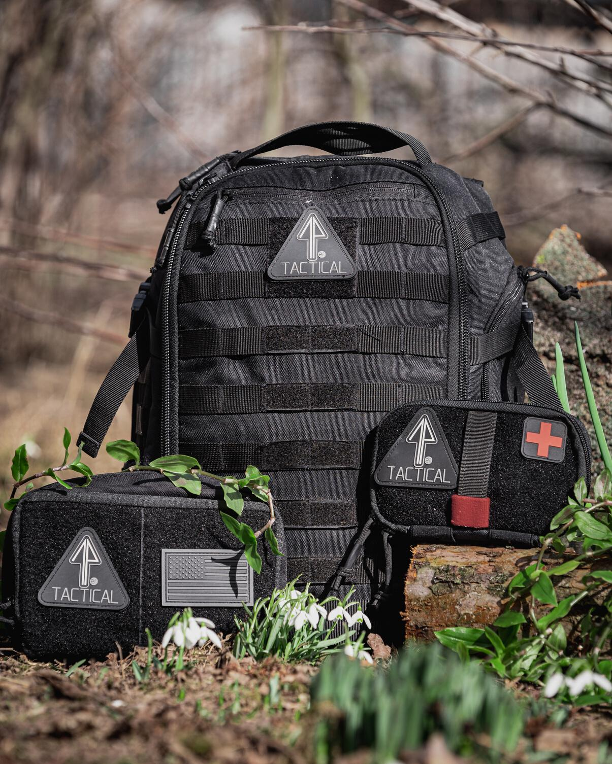 A man is outdoors camping with his 14er Tactical Backpack and gear.