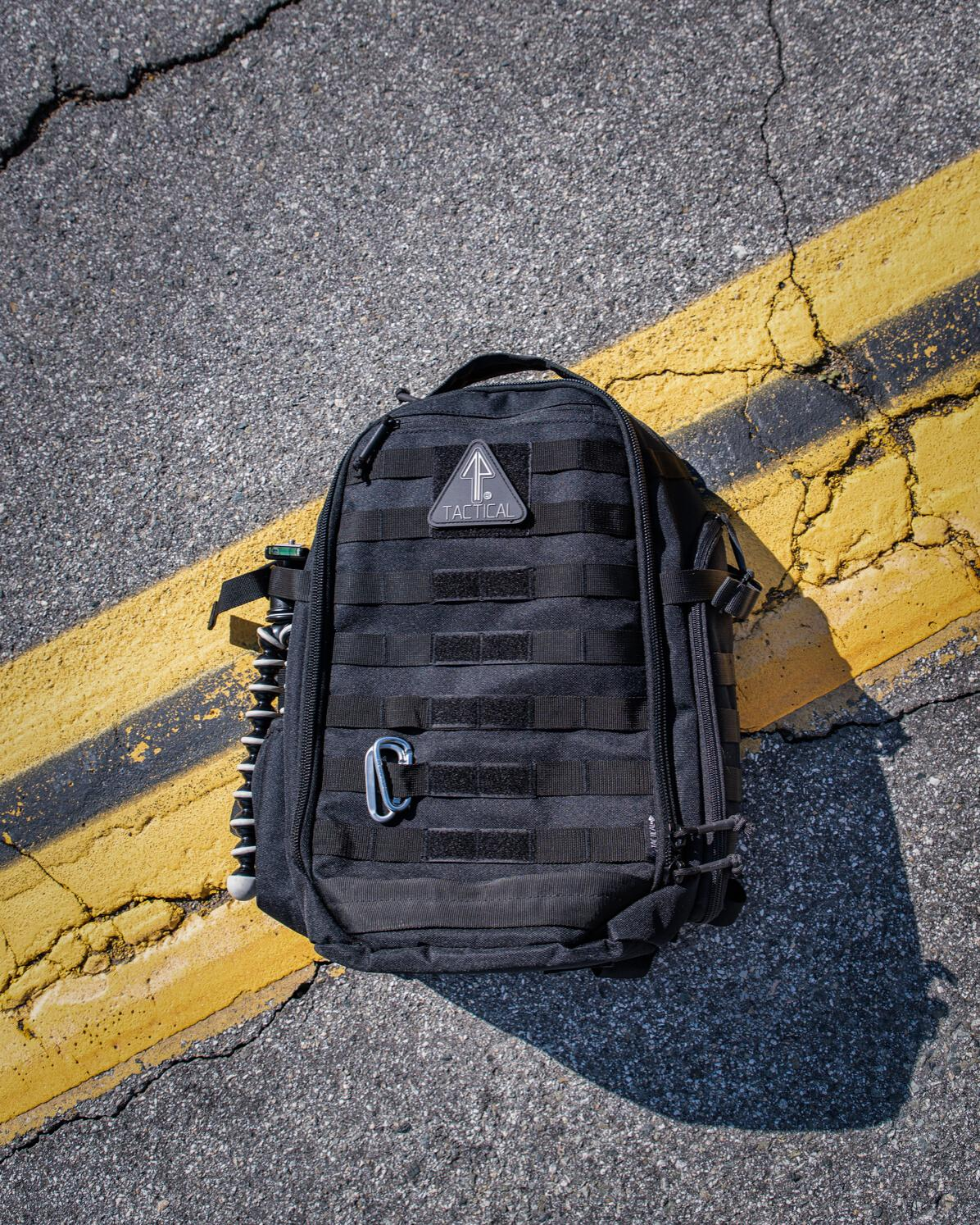 A 14er Tactical Backpack is laid on the street, well-cleaned and maintained.