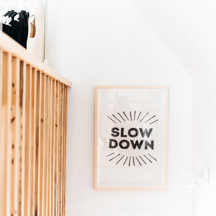 Slow Down Tea Towel Framed And Hanging On White Wall