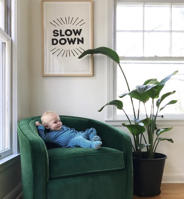 Slow Down Tea Towel Framed Hanging On Wall With Green Chair And Plant