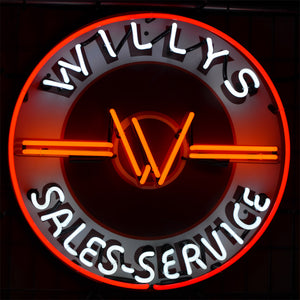 "Willys Brand Sales-Service neon sign showing the ""W"" logo in the center"