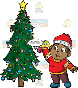 Young James Putting Ornaments On A Tree. A black boy wearing burgundy pants, a red with yellow sweaters, blue shoes, and a red and white hat, reaching up to put a Christmas ornament on a tree