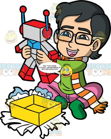 Young Simon Taking A Toy Out Of A Gift Box. An Asian boy wearing pink pants, a green sweater, green socks, and an orange and white scarf, sitting on the floor and smiling after taking a toy robot out of a gift box