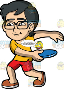 Young Simon About To Throw A Frisbee. An Asian boy wearing red shorts, a yellow shirt, brown shoes, and eyeglasses, holding a blue frisbee in one hand and preparing to throw it