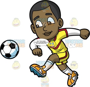 Young Calvin Kicking A Soccer Ball. A young black boy wearing yellow with red shorts, a yellow with red shirt, white socks, and orange soccer cleats, smiling as he kicks a soccer ball into the air