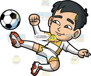 Kevin Kicking A Soccer Ball. A young Asian boy wearing white and yellow shorts, a white and yellow shirt, white socks, and soccer cleats, stretching his leg out to kick a soccer ball