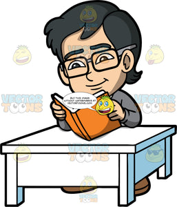 Young Simon Reading A book At School. An Asian boy wearing a gray shirt and eyeglasses, sitting at a white table reading a book with an orange cover