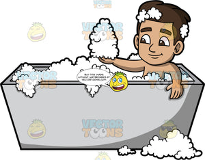 Young Gabriel Playing With Bubbles In The Tub. A Hispanic boy sitting in a gray bathtub and scooping up a handful of bubbles in his hand