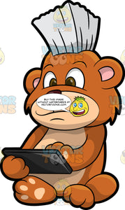 Brushy Bear Playing On A Mobile Tablet. A cute brown bear with brown eyes and a white bristle mohawk hair cut, sitting on the floor and playing a game on a tablet