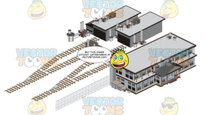 Grey Factory Building With Smokestacks And Chainlink Fence With Train Tracks Aand Smaller Storage Building Behind It