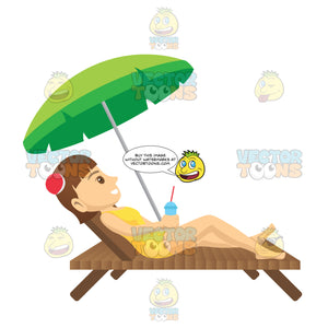 Brunette Female Tourist Laying On A Beach Chair While Holding A Drink Under An Umbrella