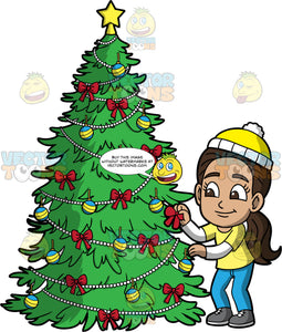 Young Isabella Trimming A Christmas Tree. A Hispanic girl wearing blue pants, a yellow t-shirt over a long sleeve white shirt, gray shoes, and yellow and white hat, putting a red bow on a Christmas tree