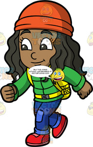 Young Maggy Hiking On A Fall Day. A young black girl wearing blue pants, a green jacket, an orange hat, red hiking shoes, and a yellow backpack, smiles while on a hike