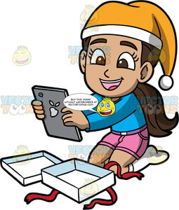 Young Isabella Admiring The Present She Just Opened. A Hispanic girl wearing pink shorts, a long sleeve blue shirt, white socks, and a yellow and white hat, smiles widely as she holds the tablet she just received in her hands