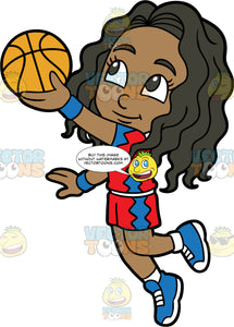 Young Maggie Jumping Up To Try And Get The Ball In The Net. A young black girl wearing red with blue shorts, a red with blue shirt, and blue running shoes, jumping and trying to toss the basketball in the net