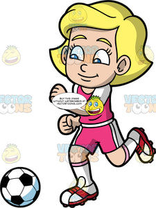 Young Mary Getting Ready To Kick A Soccer Ball. A young blonde girl wearing pink shorts, a pink and white shirt, white socks, and white and red soccer cleats, running down the field and getting ready to kick a soccer ball