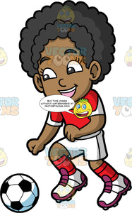 Young Jackie Chasing After A Soccer Ball. A young black girl wearing white shirts, a red with white shirt, red socks, and soccer cleats, smiles and runs after a soccer ball