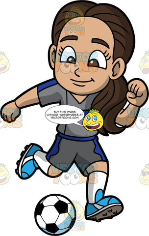 Young Isabella Preparing To Kick A Soccer Ball. A young Hispanic girl wearing dark gray with blue shorts, a dark gray with blue shirt, white socks, and blue soccer cleats, running after a soccer ball and getting ready to kick it