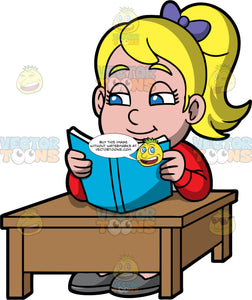 Young Pat Reading A Book At School. A blonde girl wearing a red shirt, sitting at a brown table reading a book with a blue cover