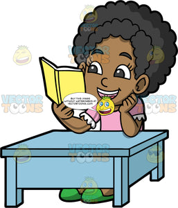 Young Jackie Sitting At A Table Reading. A black girl wearing a pink shirt, sitting at a blue table reading a book with a yellow cover