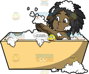Young Lisa Blowing On Bubbles In The Bath. A black girl sitting in a bathtub filled with bubbles and blowing on some bubbles in her hand