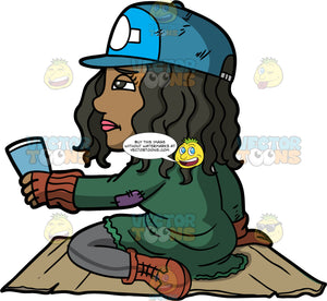 Maggy Holding A Cup Out Asking For Spare Change. A homeless woman wearing gray pants, a green jacket, brown boots, and a blue baseball cap, sitting on a piece of cardboard, holding a paper cup and asking people for change