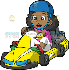 A Pretty Black Girl Races Around On A Yellow Go-Kart. A black girl wearing a blue helmet, pink shirt, white pants and red shoes, competently steers a bright yellow go-kart