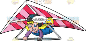 A Blonde Girl Piloting A Hang Glider. A happy girl with blonde hair and blue eyes, wearing a helmet with a camera attached to it, hangs onto the bar of a pink striped hang glider