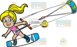 A Happy Blonde Girl Being Pulled Across The Water On Her Kiteboard. A blonde girl wearing a pink bathing suit, and strapped onto a blue and white kiteboard, holds onto a bar attached to a green and blue power kite
