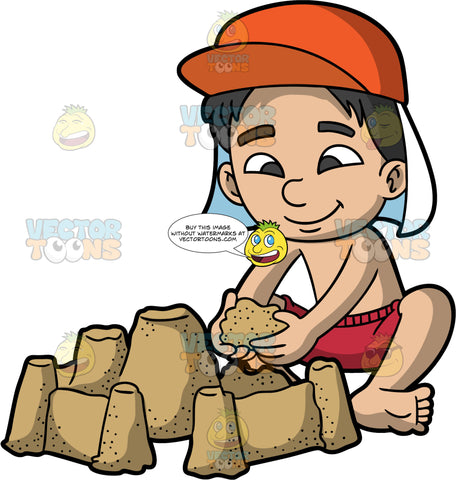 A Boy Having Fun Building A Sandcastle. A boy wearing red swim trunks, no shirt and an orange sun hat, sitting in the sand adding a handful of sand to the sandcastle he is building