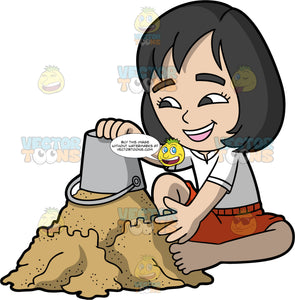 An Asian Girl Dumping A Bucket Of Sand On Top Of Her Sandcastle. An Asian girl with black hair and dark brown eyes, wearing red shorts and a white shirt, sitting in the sand and emptying a bucket of sand on top of the sandcastle she is building