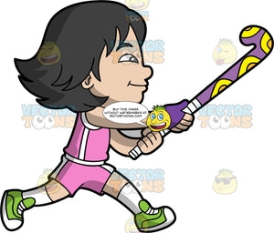 An Asian Girl Playing Field Hockey. An Asian girl with black hair, wearing pink and white shorts, a pink and white shirt, white socks, and green shoes, holds a field hockey stick up after just hitting a ball