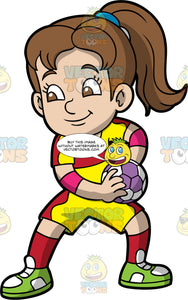 A girl getting ready to start a handball match. A girl with brown hair in a ponytail, wearing yellow and red shorts, a yellow and red shirt, red socks, Green shoes, and pink elbow pads, holds a purple and white handball in her hands in preparation for starting a game